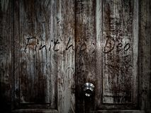 Door to the hell. Finit hic, Deo Latin translating roughly, Here ends God wording on Wooden old vintage grunge door texture background. Horror concept royalty free stock images
