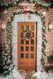 The door to the house with Christmas wreath. House decorated in Christmas style stock photos