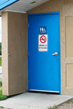 The door to a multisex restroom with a no smoking sign.  Royalty Free Stock Image
