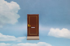 Door to new world. Close door on blue sunny sky with fluffy clouds. Stock Image