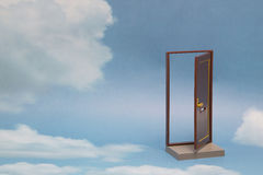 Door to new world. Open door on blue sunny sky with fluffy clouds. Stock Photo