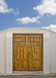 Door to the Sky. Wooden door on a white wall leading into a beautiful sky Royalty Free Stock Image