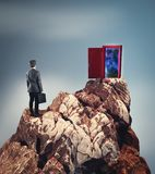Door to space. Businessman standing on a mountain peak in front of a opened door to the space royalty free stock photography