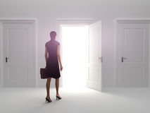 Door to success. Business female choosing the entrance to an open door Royalty Free Stock Photography