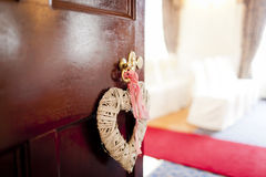 Door to wedding ceremony. Decorative love heart on open door with room ready for wedding ceremony in background Royalty Free Stock Photography