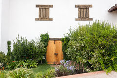 Winery in Colchagua Valley Chile. A door and two wood windows on a white wall and the garden with pink blooming flowers in a winery in Colchagua Valley, Chile stock photography