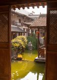 Door view of the green pond in center of abandoned chinese hotel with traditional style architecture. Stock Image