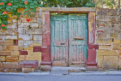 Door on vintage house stone wall facade. Pale green door on vintage house stone wall facade Royalty Free Stock Photos