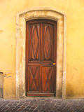Door in the wall. Exterior panelled wooden door in arched weathered stone doorway, southern France Stock Photo