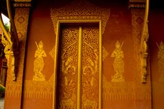 The door and wall painting.Buddhist temple with gold.Luang Prabang.Laos. Royalty Free Stock Photos