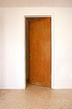 Door in white wall slightly open Stock Image