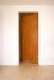 Door in white wall slightly open. A wooden door is slightly open on a white wall, terrazzo floor Stock Image