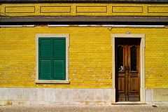 Door and window. Green window on yellow traditional Portuguese house Royalty Free Stock Photo