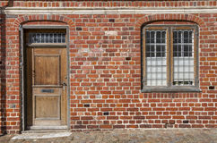 Door and window on red brick wall. Door made of wood and window with bars on a red brick wall in Denmark Stock Photo