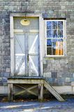 Door and window on slate shingled building royalty free stock image