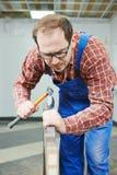 Door works with hummer and chisel. Carpenter installer works with hammer and chisel at interior wood door installation stock photos