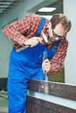 Door works with hummer and chisel. Carpenter installer works with hammer and chisel at interior wood door installation stock image