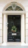 Door wreath. Luxurious front door with conifer Christmas wreath Stock Photos