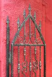 Door of wrought iron. And red wall Stock Photo