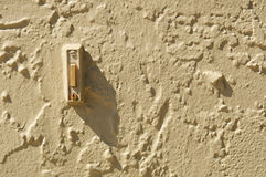Doorbell in stuccoed wall with shadow and copy space Royalty Free Stock Photography