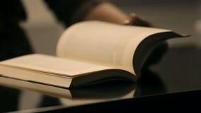 Doorbladerende het boekpagina's van de vrouwenhand stock video