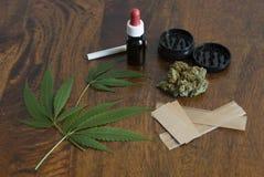 Doorbladert het cannabis sativa onkruid en bloemknoppen op houten achtergrond met molen en groot rokend document Stock Afbeeldingen