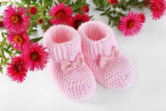 Doorboor weinig babyschoenen met bloemen op een wit stock afbeeldingen