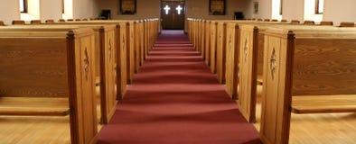 Doorgang van traditionele Christelijke kerk met lege banken stock foto's