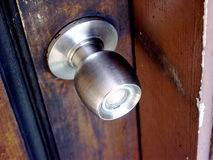 Doorknob. Shiny, brushed metal doorknob against a rustic wood front door Royalty Free Stock Photos