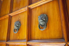 Doorknob with lion head on wooden door Stock Photos