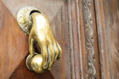 Doorknob with the shape a hand on an old wooden door Stock Photography