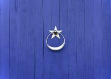 Doorknob with silver star. Blue door with  silver star doorknob Stock Photo