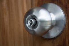 Doorknob silver stick blacked beautiful brown wooden door. Royalty Free Stock Photo