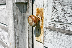 Doorknob in the Sun. The rusted doorknob of a worn, old door. White paint peels from wood of the weathered doorframe Royalty Free Stock Photos