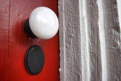Doorknob velho na porta vermelha antiga da HOME histórica Fotografia de Stock