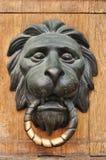 Doorknocker with head of lion. Doorknocker with bronze head of lion on wooden background Stock Photography