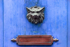 Doorknocker and letter box on a blue wooden door Stock Photo