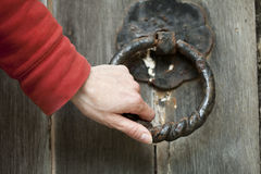 Doorknocker and hand. Doorknocker on old church door Royalty Free Stock Image