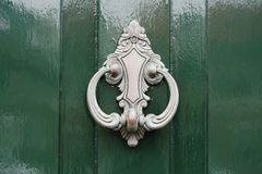 Doorknocker in silver on green painted wooden door Stock Photography