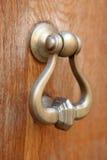 Doorknocker. A doorknocker on a wooden door Royalty Free Stock Images