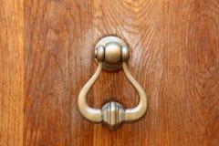 Doorknocker. A doorknocker on a wooden door Stock Images