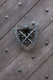 Doorknocker on the wooden gate fixed with rivets Royalty Free Stock Photo