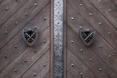 Doorknockers on the wooden gate fixed with rivets Stock Photography