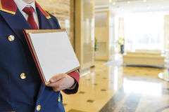 The doorman in the lobby of the hotel holding a sign. The doorman in the form in the lobby with a sign with the announcement Royalty Free Stock Photo