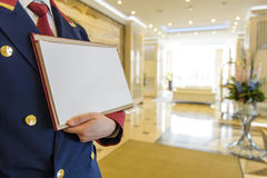 The doorman in the lobby of the hotel holding a sign. The doorman in the form in the lobby with a sign with the announcement Royalty Free Stock Photos