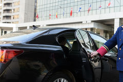 The doorman opens the door of a luxury car. Near the hotel, business class Royalty Free Stock Photos