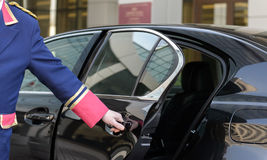 The doorman opens the door of a luxury car. Near the hotel, business class Stock Image