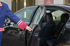 The doorman opens the door of a luxury car Royalty Free Stock Photography
