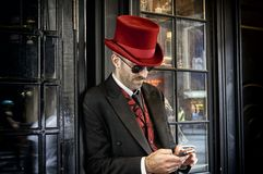 Doorman in Red Top Hat. New York, MA - July 11 2013 - Creepy doorman dressed in tuxedo and red top hat using cell phone outside the Jekyll and Hyde Club off Royalty Free Stock Images
