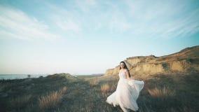 Doornemende bruid in verbazende lange kleding het landschap stock footage